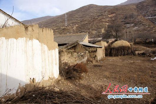 """甘肃漳县大草滩乡新联村,""""遮羞墙""""内农户破败的房屋和院墙与新墙形成鲜明对比"""