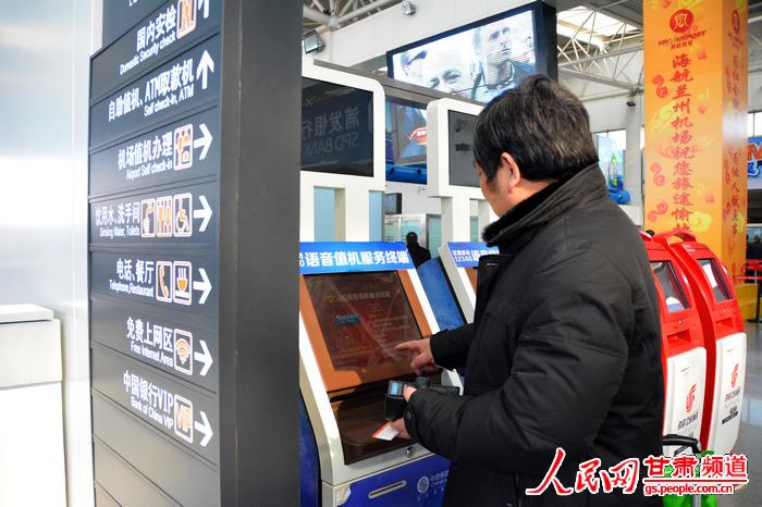 高翔/兰州中川机场,旅客正在使用自助值机终端。(高翔摄)...