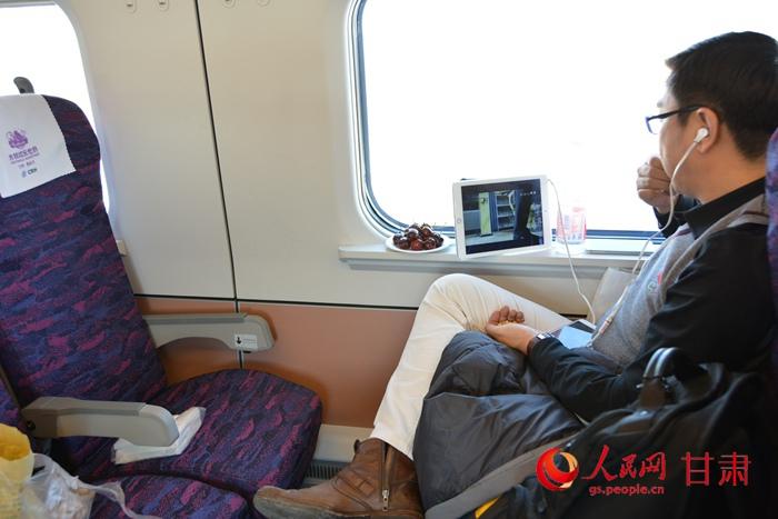 一名旅客正坐在兰州至乌鲁木齐d2703次列车