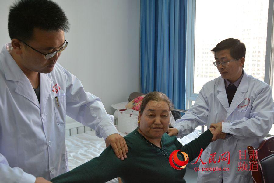 李建省(右)和徒弟一起为患者按摩(刘海天 摄)